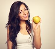 Beautiful excited makeup casual long hair brunette woman with he. Althy teeth holding the red tasty apple and looking happy. Toned closeup portrait Stock Images