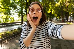 Beautiful excited shocked woman outdoors take a selfie by camera. stock image