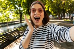 Beautiful excited shocked woman outdoors take a selfie by camera. stock photos