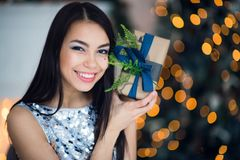Beautiful excited smiling young woman with present gift feeling happy near christmas tree. Close-up portrait Stock Image