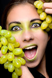 Beautiful excited woman holding green grapes royalty free stock photography