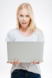 Beautiful excited woman holding laptop isolated. On a white background Stock Photo
