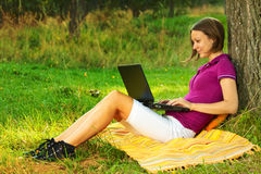 Beautiful excited woman with a laptop in the park. Beautiful woman sitting on the ground near a tree and working on a laptop. Horizontal shot with copyspace Royalty Free Stock Photography
