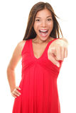 Beautiful excited woman pointing. Woman pointing energetic at camera excited and happy. Isolated portrait of young cheering Asian / Caucasian female model in red Royalty Free Stock Image