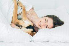 Beautiful excited woman and her cute cur dog are fool around, looking at camera while lying covered with a blanket in bed. stock photos