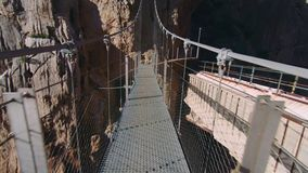 Walking on dangerous path in national park. Beautiful exciting and scary hanging suspension bridge over abyss on high height between rocks and cliffs. One of stock video