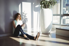 Beautiful executive sitting on floor and using mobile phone Stock Photo