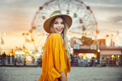 Beautiful exited smiling tourist woman having fun at amusement park at hot summer day trip on the beach.  Stock Image