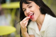 Beautiful exited woman eating strawberry lunch out of office on city street on public place. royalty free stock image