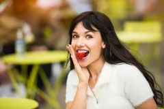 Beautiful exited woman eating strawberry lunch out of office on city street on public place. stock photo