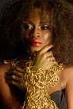 Beautiful exotic African American woman with a curly afro hairstyle wearing gold makeup and choker looking away Royalty Free Stock Photos