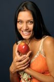 Beautiful exotic woman with apple. Beautiful Exotic Woman is eating and holding the apple Stock Images