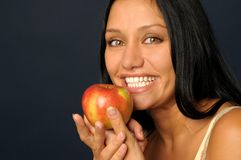 Beautiful exotic woman with apple. Beautiful Exotic Woman is eating and holding the apple Royalty Free Stock Image