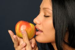 Beautiful exotic woman with apple. Beautiful Exotic Woman is eating and holding the apple Stock Photo