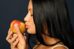 Beautiful exotic woman with apple. Beautiful Exotic Woman is eating and holding the apple Stock Image