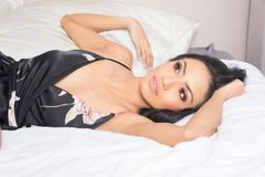 Beautiful woman lying on bed wearing dress stock photo