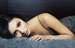 Beautiful exotic woman. Beautiful young exotic modern woman lying on bed Stock Photo