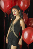 Beautiful exotic young woman. In black dress red balloons Stock Image