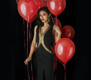 Beautiful exotic young woman. In black dress red balloons Stock Photography