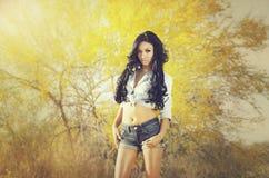 Beautiful exotic young woman long hair. Beautiful exotic young woman wearing denim jean shorts and top - posing in Arizona desert, USA Stock Images