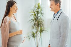 Beautiful expectant mother visiting pediatrician royalty free stock image