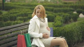 Beautiful expectant sitting city bench with shopping bags and smiling, baby care. Stock footage stock video