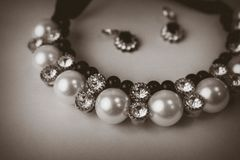 Beautiful expensive precious shiny jewelry fashionable glamorous jewelry, necklace and earrings with pearls and diamonds. Diamonds on a black and white royalty free stock images