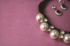 Beautiful expensive precious shiny jewelry fashionable glamorous jewelry, necklace and earrings with pearls and diamonds. Diamonds on a pink purple background stock image