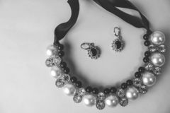Beautiful expensive precious shiny jewelry fashionable glamorous jewelry, necklace and earrings with pearls and diamonds. Diamonds on a black and white royalty free stock photography