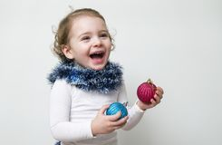 Beautiful expressive happy cute laughing smiling baby infant face with christmas toys. On a white background Royalty Free Stock Photos
