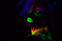 Beautiful extraterrestrial model woman with blue hair and green lips in neon light. It is close portrait of beautiful Stock Images
