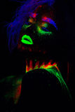 Beautiful extraterrestrial model woman with blue hair and green lips in neon light. It is portrait of beautiful model Stock Photo