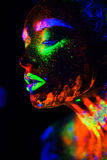Beautiful extraterrestrial model woman in neon light. It is portrait of beautiful model with fluorescent make-up, Art Royalty Free Stock Photos
