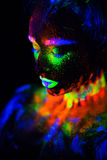 Beautiful extraterrestrial model woman in neon light. It is portrait of beautiful model with fluorescent make-up, Art Royalty Free Stock Images