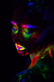 Beautiful extraterrestrial model woman in neon light. It is portrait of beautiful model with fluorescent make-up, Art. Close up beautiful extraterrestrial model Royalty Free Stock Photography