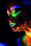 Beautiful extraterrestrial model woman in neon light. It is portrait of beautiful model with fluorescent make-up, Art Stock Images