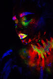 Beautiful extraterrestrial model woman in neon light. It is portrait of beautiful model with fluorescent make-up, Art Royalty Free Stock Image