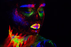 Beautiful extraterrestrial model woman in neon light. It is portrait of beautiful model with fluorescent make-up, Art Royalty Free Stock Photography