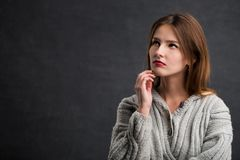 Beautiful Eye-catching Girl. Portrait of beautiful serious girl in gray sweater, indoor shot in the gray background Stock Photo
