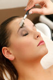 Beautiful eyebrows. Cosmetician draws the shape of the eyebrows for a client Stock Photo