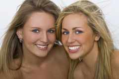 Beautiful Eyes & Smiles. Two beautiful young women with stunning blue eyes and toothy smiles stock image