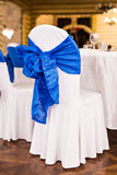 Beautiful fabric bow on the chair. Wedding restaurant for marriage. White decor for bride and groom. Colorful decoration Royalty Free Stock Images