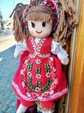 Beautiful fabric doll in red traditional dress with flowers stock image