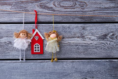 Beautiful fabulous fairies and red house hanging on a wooden fen royalty free stock photos