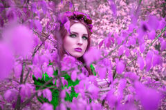 A beautiful and fabulous girl in a pink foliage with red wreath Stock Photo