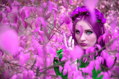 A beautiful and fabulous girl in a purple foliage with red wreath Royalty Free Stock Image