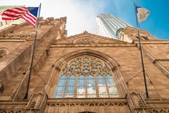 Beautiful facade seen from below with gorgeous sky. In Manhattan with two flags stock images