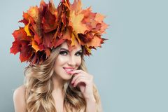 Beautiful face. Autumn woman with fall leaves on gray background.  royalty free stock images