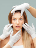 Beautiful face being examinated plastic surgeons h Royalty Free Stock Images