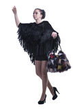 Fashionable woman walking in black poncho with colorful fur bag and high-heel shoes Stock Photos